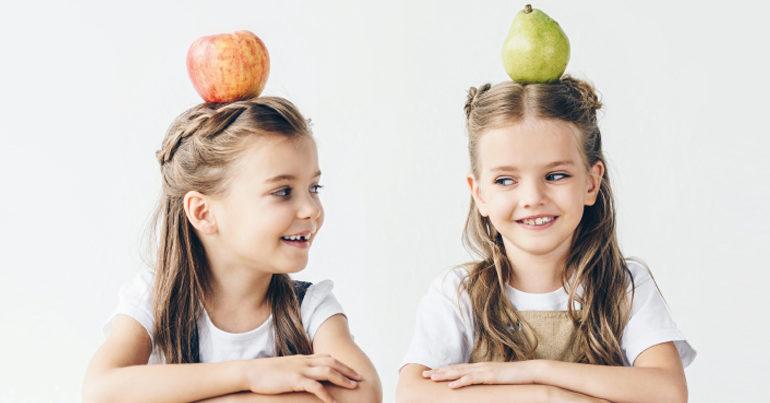 Zwei Mädchen mit einem Apfel und einer Birne auf dem Kopf